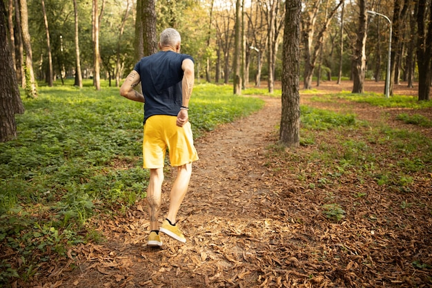 Siwy mężczyzna biegający samotnie w lesie
