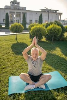 Siwy mężczyzna praktykuje jogę, podnosząc ręce nad głowę