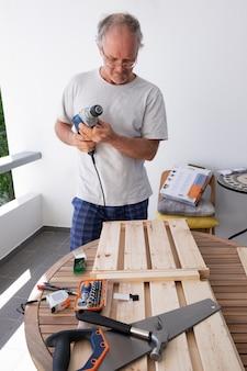 Siwy mężczyzna trzyma elektryczny śrubokręt w szkłach