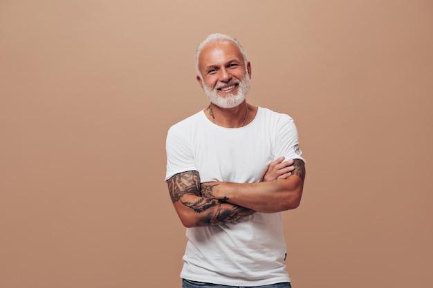 Siwy mężczyzna w białej koszulce pozuje na beżowej ścianie