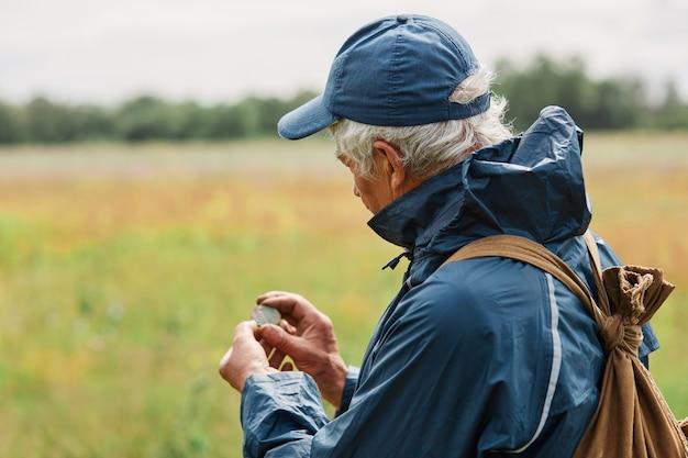 Siwy mężczyzna w kurtce i czapce poszukiwacz skarbów, patrząc na swoje znalezisko, trzymając starą monetę pod ziemią podczas wyszukiwania na łące lub polu.