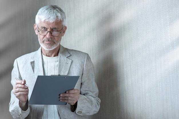 Siwy mężczyzna w lekkich ubraniach i okularach zawiera umowę na papierze