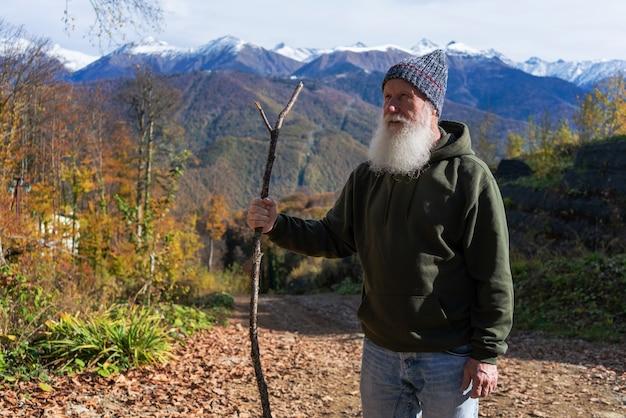Siwy mężczyzna z brodą podbija szczyt, pojęcie turystyki i rekreacji na starość