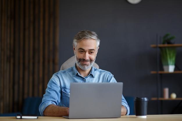 Siwy starszy mężczyzna pracujący w domowym biurze z laptopem. biznesowy portret przystojny menedżer siedzi w miejscu pracy. nauka online, kursy online. pomysł na biznes.