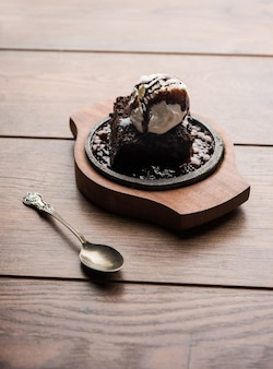 Sizzling chocolate brownie to słodkie danie przyrządzane z gałki lodów na wierzchu podawane z dużą ilością rozpuszczonej czekolady. serwer gorący. selektywne skupienie