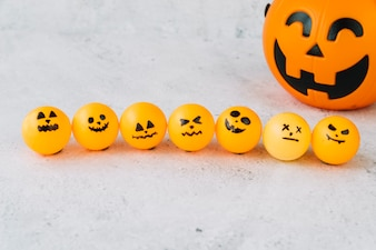 Skład z małą pomarańczową piłką z strasznymi twarzami w rzędzie