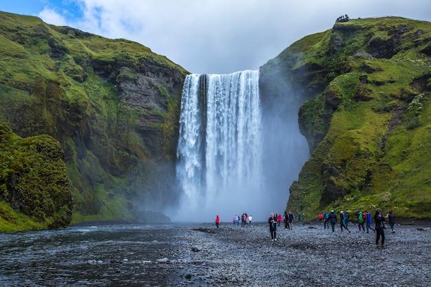 Skãƒâ³gafoss, islandia â »; sierpień 2017: młody człowiek pod wodospadem z otwartymi ramionami i pięknym otoczeniem