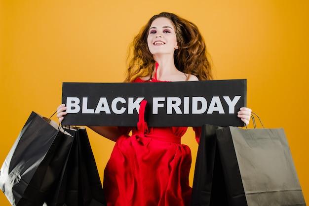 Skacząca dziewczyna ma czarny piątek znak z papierowymi torbami na zakupy izolowanymi na żółtym