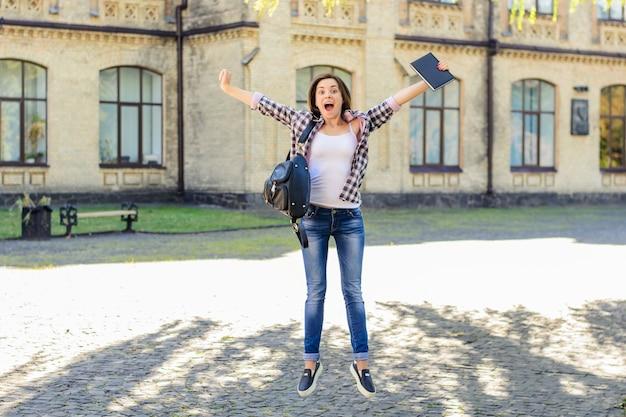 Skacząca dziewczyna z tłem kampusu książki i torby