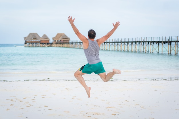 Skaczący mężczyzna na tropikalnej plaży