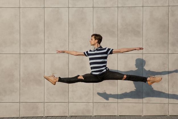 Skaczący młody biznesmen przed budynkami, w biegu w skoku wysoko