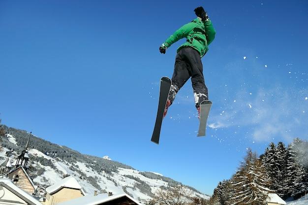 Skaczący narciarz bawiący się zimą w górach