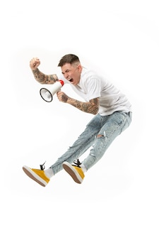 Skaczący wentylator na białym tle. młody człowiek jako kibic piłki nożnej z megafonem