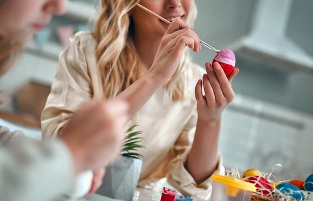Skadrowany obraz młodej kobiety z małą ładną dziewczyną i chłopcem przygotowują się do obchodów wielkanocy. szczęśliwa rodzina w uszach króliczka spędza razem czas przed wielkanocą podczas malowania jajek.