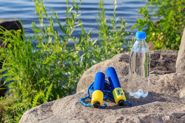 Skakanka i butelka z wodą na skale z tłem nasypu rzeki. lato, aktywny tryb życia