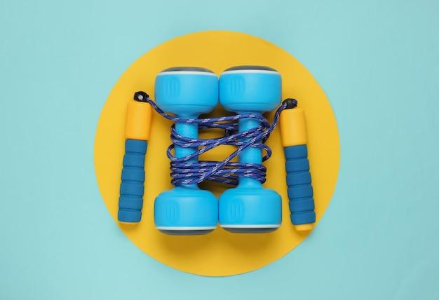 Skakanka owinięta hantlami na żółty niebieski pastel
