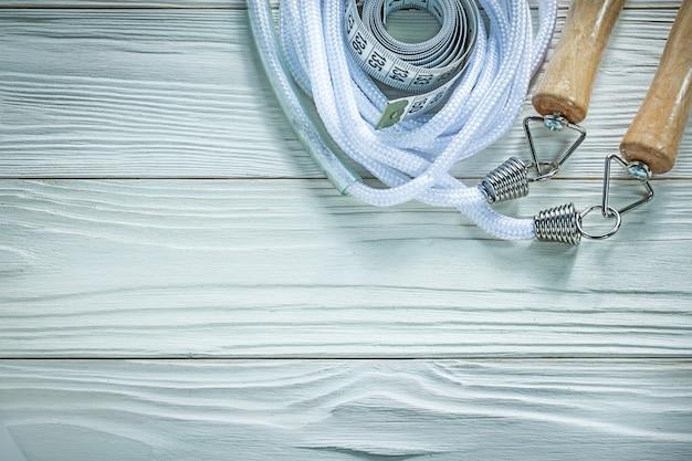 Skakanka taśma miernicza na drewnianej desce fitness koncepcja
