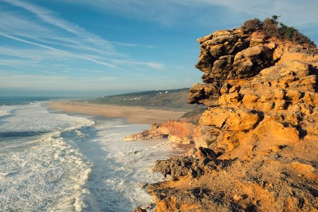 Skała i plaża z falami na wybrzeżu oceanu atlantyckiego w pobliżu miasta nazare w portugalii o zachodzie słońca