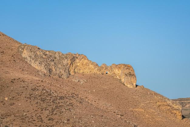 Skała o dziwacznym kształcie w pustynnym krajobrazie na tle błękitnego nieba.