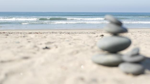 Skała równoważąca oceaniczną plażę, kamienie układające się przez fale wody morskiej. piramida kamyków na piaszczystym brzegu