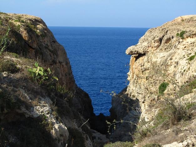 Skała w kształcie litery v i czyste morze w ciągu dnia w wied il-mielah, gharb, gozo, wyspy maltańskie
