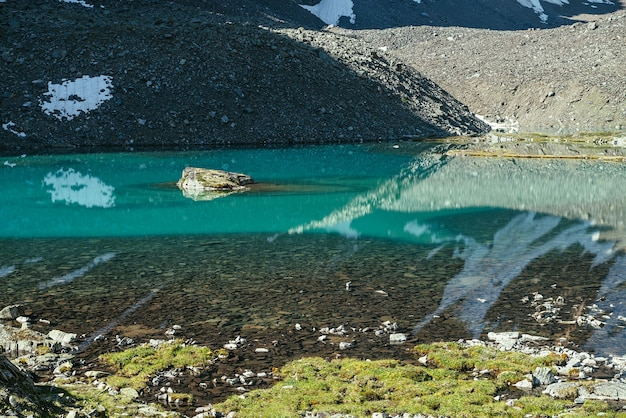Skała w turkusowym górskim jeziorze. śnieżna góra odbita w lazurowej, czystej wodzie lodowcowego jeziora. piękne słoneczne tło z śnieżnobiałym odbiciem lodowca w zielonej tafli wody jeziora górskiego.