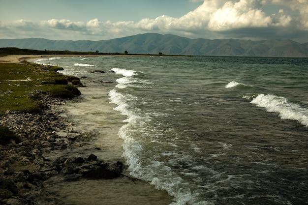 Skalista plaża nad jeziorem z ciemnym abstrakcyjnym niebem