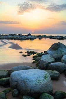 Skalista plaża zatoki ryskiej na zachód słońca. kamienne wybrzeże vidzeme na łotwie.
