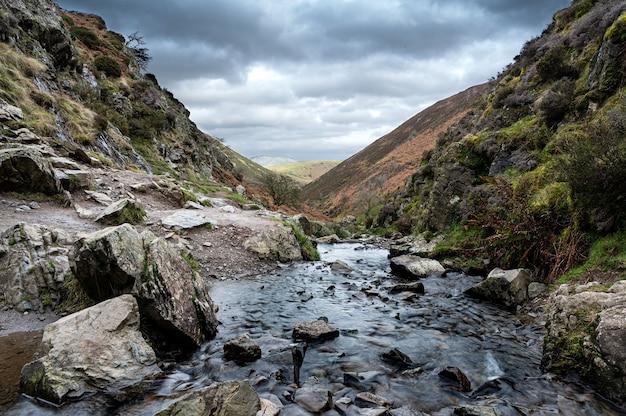 Skalista rzeka przepływająca przez góry z ciemnymi chmurami
