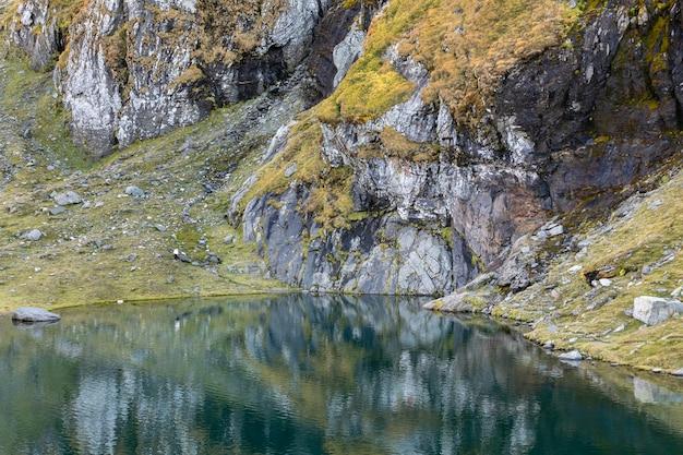 Skaliste brzeg odbicie lustrzane w spokojnym górskim jeziorze balea