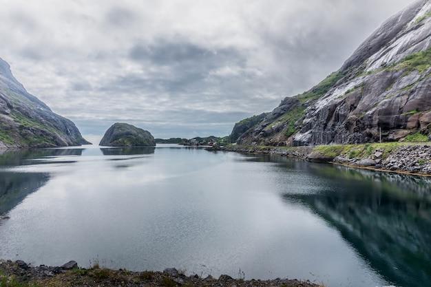 Skaliste brzegi odbijają się w wodzie wieczorem. narodowy szlak turystyczny lofoty, norwegia