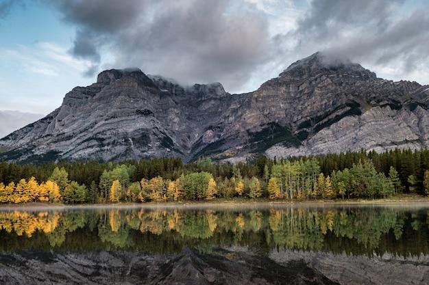 Skaliste góry z jesiennym lasem sosnowym i chmurami wiejącymi na wedge pond w kraju kananaskis, kanada