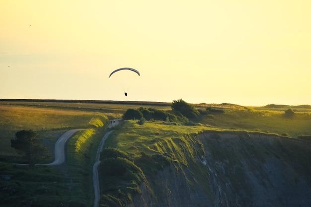 Skaliste klify pokryte zieloną trawą o zachodzie słońca. mężczyzna ćwiczący nad nimi paralotniarstwo.