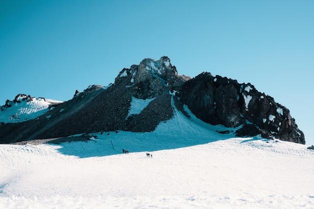 Skaliste śnieżne góry pod pięknym niebieskim niebem