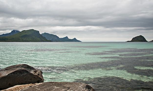 Skaliste wybrzeże, piaszczysta plaża z turkusową wodą, archipelag lofoty, norwegia