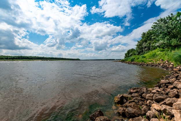 Skaliste wybrzeże rzeki. krajobraz wsi rzeki. duże kamienie na brzegu rzeki.