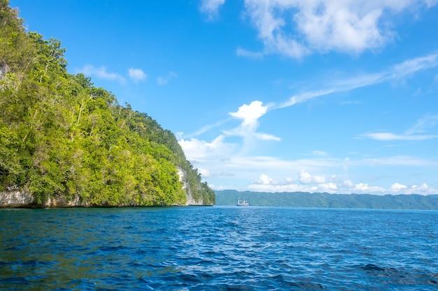 Skaliste wybrzeże tropikalnej wyspy indonezji przy słonecznej pogodzie. las deszczowy na stoku. jacht na odległość