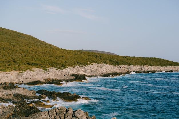 Skaliste wybrzeże w pobliżu kempingu veslo w czarnogórze lazurowo-niebieska woda białe fale uderzające o skały w słońcu