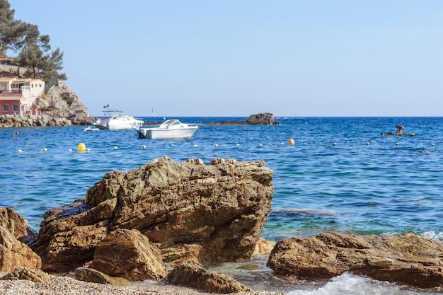 Skalisty brzeg morza z kamienistej plaży, fale, błękitne niebo