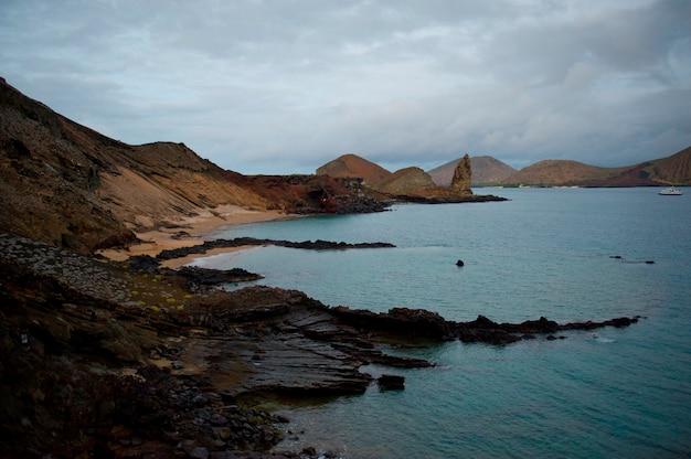 Skalisty wybrzeże z pinakli skałą w tle, bartolome wyspa, galapagos wyspy, ekwador