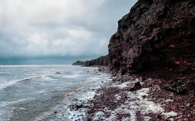 Skalny klif nad wodą z pływową linią brzegową. tersky brzeg morza białego .. widok panoramiczny. rosja.