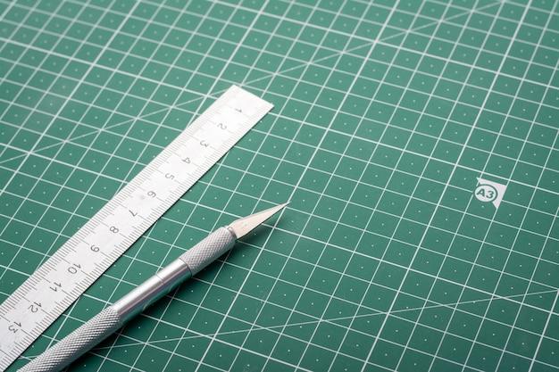Skalpel do cięcia papieru i linijki na tle maty do cięcia