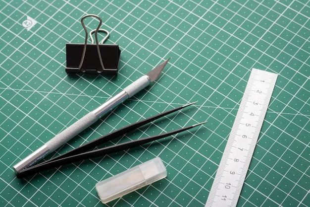 Skalpel, pinceta, linijka, spinacz biurowy i pudełko z ostrzami do noża na macie do cięcia