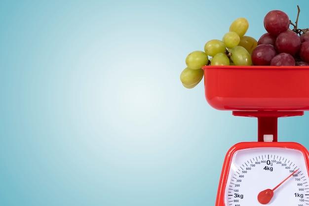 Skaluj z czerwonymi i zielonymi winogronami na pastelowym niebieskim tle z miejscem na tekst po jednej stronie