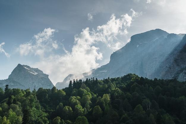 Skały i przełęcz z błękitnym niebem z promieniami słońca przebijającymi się przez chmury. fiszt oszten to szczyt górski w zachodniej części głównego grzbietu kaukaskiego