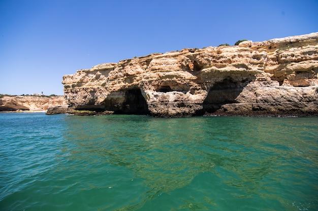 Skały, klify i krajobraz oceanu na wybrzeżu w aalgarve, portugalia widok z łodzi