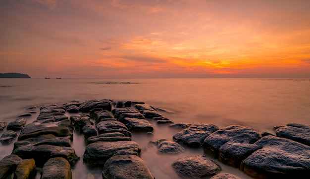 Skały na kamień plaży o zachodzie słońca. piękne niebo zachód słońca na plaży. zmierzch morze i niebo. tropikalne morze o zmierzchu. dramatyczne niebo i chmury.