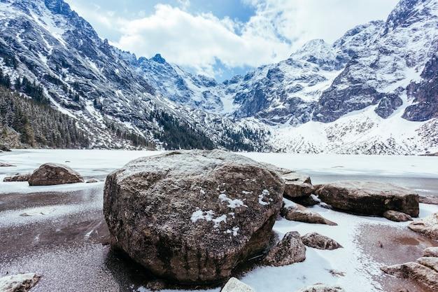 Skały nad jeziorem z górami w zimie