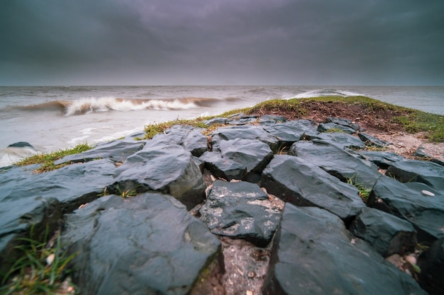 Skały pokryte mchami i wieczorem otoczone falującym morzem pod zachmurzonym niebem