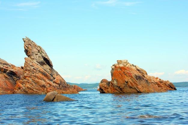 Skały w błękitnym morzu, oświetlone przez słońce. tło.